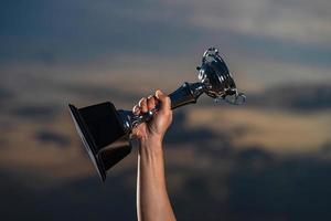 een man die een trofeekop tegen de bewolkte hemelachtergrond van de schemering houdt foto