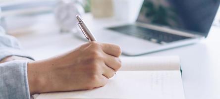 vrouw schrijven in planner notebook tijdens het gebruik van laptop om te werken foto