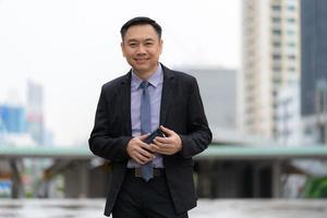 Aziatische zakenman permanent en bedrijf mobiele telefoon met zakelijke kantoorgebouwen op de achtergrond van de stad