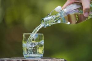 hand drinkwater uit de fles gieten in glas met natuurlijke achtergrond foto