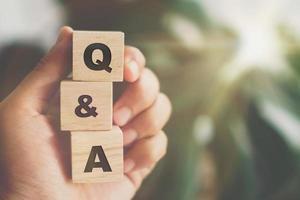 q en een alfabet op houten blokjes in de hand foto