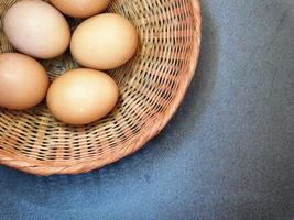bruine eieren in een rieten mand op een blauwe tafelachtergrond