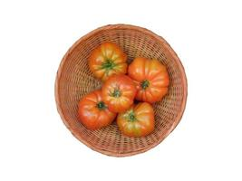 tomaten in een rieten mand op een witte achtergrond foto