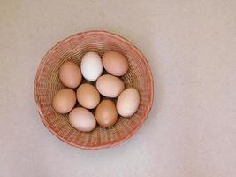 bruine eieren in een rieten mand op een lichte tafel achtergrond