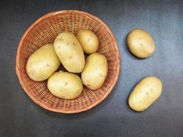 aardappelen in een rieten mand op een donkere tafel achtergrond foto