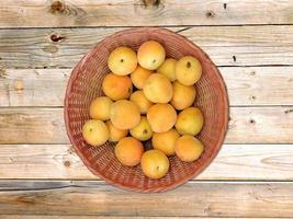 abrikozen in een rieten mand op houten tafel achtergrond foto