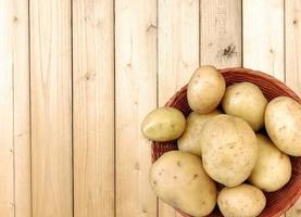 aardappelen in een rieten mand op een houten tafel achtergrond foto