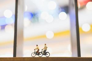 miniatuurreizigers met fietsen op een houten brug