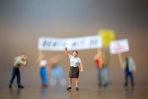 miniatuurmenigte van demonstranten die hun handen opheffen en op een houten achtergrond schreeuwen foto