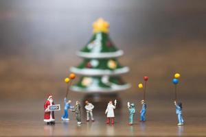miniatuur gelukkige familie die kerstmis, kerstmis en gelukkig nieuwjaarconcept viert foto