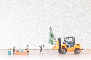 groep miniatuurarbeiders die een kerstboom voorbereiden, het concept van kerstversieringen