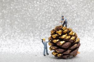 miniatuurarbeiders die een concept van de Kerstmisdennenappel, Kerstmis en Gelukkig Nieuwjaar voorbereiden foto