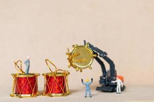 miniatuurarbeiders die werken aan kerstversiering, kerstmis en gelukkig nieuwjaarsconcept foto