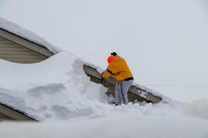 VS 2019- een man reinigt sneeuw van het dak van een huis na een sneeuwstorm foto