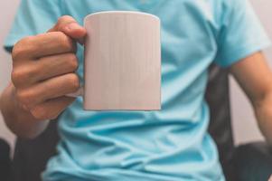 een man met een koffiekopje foto