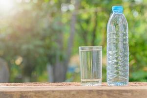 fles drinkwater en glas met natuurlijke achtergrond foto