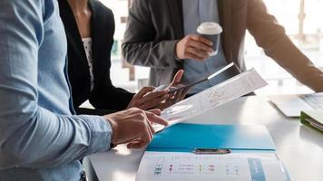 zakenmensen die een vergadering hebben en grafieken bespreken