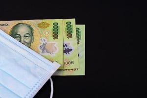 gezichtsmasker met Vietnamees geld op zwarte achtergrond foto
