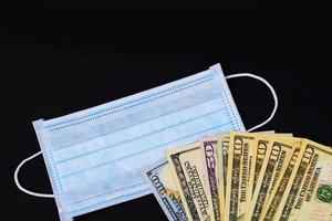 gezichtsmaskers op zwarte achtergrond met dollars foto