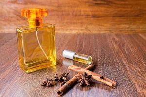 flessen parfum, kaneelstokjes en anijszaadjes op een houten tafel foto