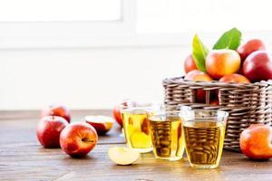 appelsap in glazen en appels in de mand foto
