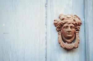 deurknop met gedecoreerd gezicht van metaal op een blauwe houten deur foto
