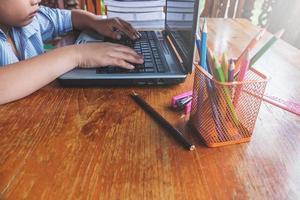 jongen die aan laptop naast kop van potloden op een houten bureau werkt
