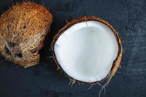 kokosnoot in tweeën gesneden op een zwarte tafel achtergrond