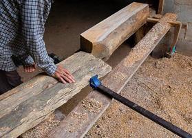 man aanpassen van een plank van hout in een houtbewerkingswinkel foto