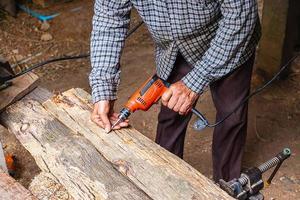 man met boormachine op de plank van hout in een houtbewerkingswinkel foto