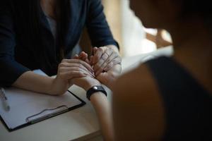 beroepsbeoefenaar in de gezondheidszorg hand in hand van een patiënt foto
