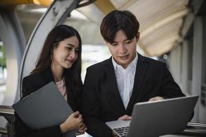 man en vrouw kijken naar een laptop foto