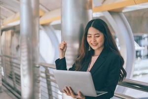 vrouw met behulp van een laptop op een treinstation foto