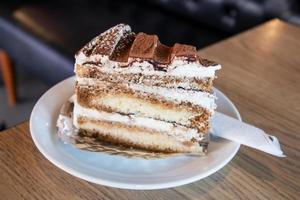 een stuk tiramisu-cake op een witte schotel