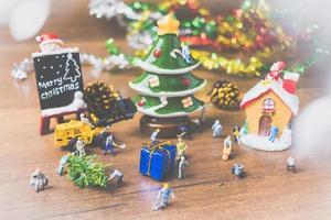 miniatuurmensen die kerstversieringen maken op een houten achtergrond foto