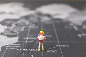 miniatuur backpacker lopen op een wereldkaart, toerisme en reisconcept