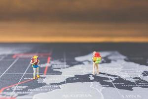 miniatuur backpackers lopen op een wereldkaart, toerisme en reisconcept