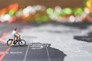 miniatuurreiziger fietsen op een wereldkaart, reizen en het wereldconcept verkennen foto