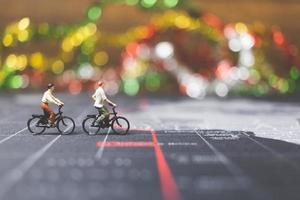 miniatuurreizigers fietsen op een wereldkaart, reizen en het wereldconcept verkennen foto