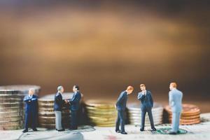 miniatuurzakenlieden op geld op een houten achtergrond foto