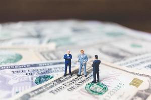 miniatuur bedrijfsmensen met Amerikaanse dollarbankbiljettenachtergrond