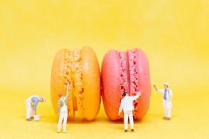 miniatuurschilders die bitterkoekjes op een gele achtergrond kleuren foto