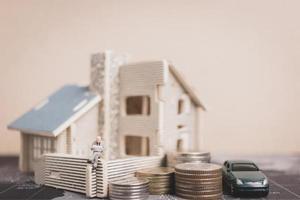 miniatuurmensen die thuis met muntstukkengeld zitten, investeringen en groei in bedrijfsconcept foto