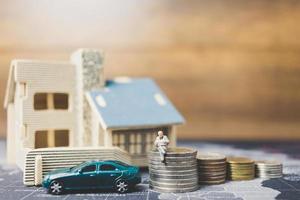 miniatuurmensen om thuis te zitten met munten, investeringen en groei in bedrijfsconcept foto