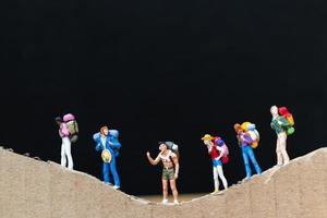 miniatuurreizigers met rugzakken die op een papieren berg-, reis- en trekkingconcept lopen foto