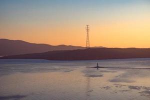 zeegezicht met zonsondergang over de tokarev-vuurtoren en de amoerbaai in vladivostok, rusland foto