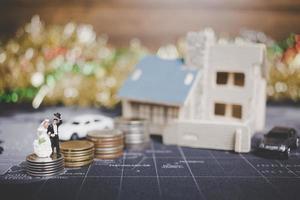 miniatuurbruid en bruidegom met muntstukken voor een huis, succesvol familieconcept foto
