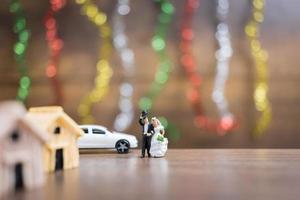 miniatuurbruid en bruidegom op een houten vloer met kleurrijke bokehachtergrond, succesvol familieconcept foto