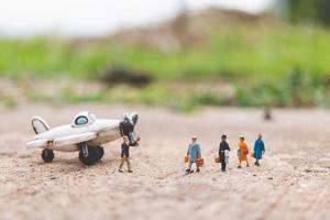 miniatuurreizigers met handbagage die in het vliegtuig stappen en het wereldconcept verkennen foto