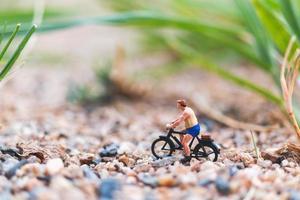 miniatuurreiziger die een fiets berijdt, het wereldconcept onderzoekt foto